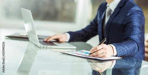successful businessman working on laptop with financial data at the workplace in a modern office. © yurolaitsalbert