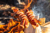 Roasted sausages on a stick over the open campfire. Outdoor food preparation