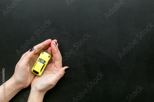 Car insurance concept. Safety of auto. Car toy in female hands on black background top view space for text - 250161903