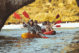 Group of happy friends walks by kayaks under big rocks in the sea. Kayaking or canoeing travel photo with group of peoples