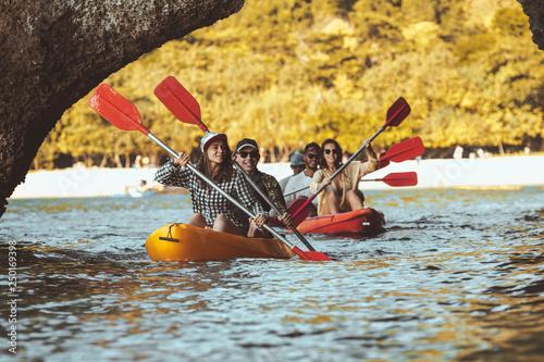 Leinwanddruck Bild Group of happy friends walks by kayaks under big rocks in the sea. Kayaking or canoeing travel photo with group of peoples