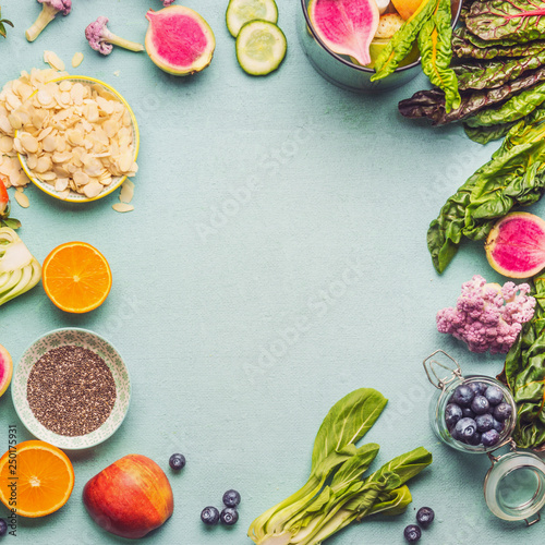Healthy smoothie ingredients on light table, top view. Various fruits , vegetables and berries with almond, chia seeds and pine nuts for tasty vegan nutrition. Smoothie preparation with blender © VICUSCHKA