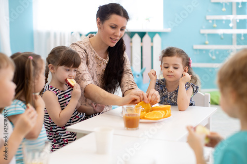 Children and carer together eating fruits in kindergarten or daycare - 250186537