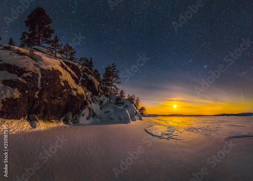 Leinwanddruck Bild Northern lights on Lake Ladoga in the Republic of Karelia. Full moon and northern lights on the lake. Night panoramas.