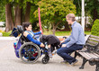 Father talking with disabled son in wheelchair outdoors at park