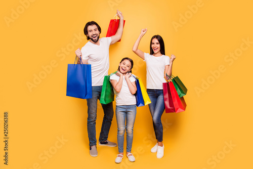 Leinwanddruck Bild Full length body size view portrait of nice attractive trendy cheerful people holding in hands bags with new clothes having fun rejoice isolated over shine vivid pastel yellow background