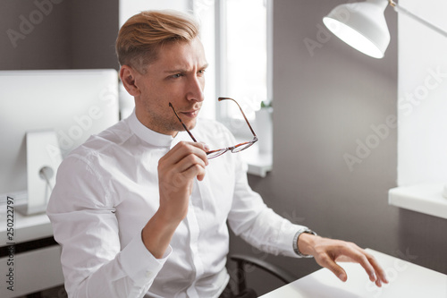 Man putting on glasses in office
