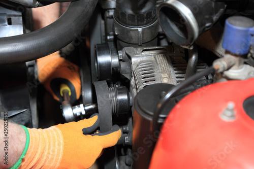 obraz lub plakat Zakładanie paska klinowego na koło alternatora.