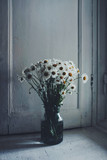 Vase with daisy flowers in vintage home interior