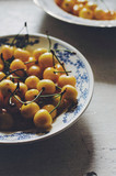 Ripe yellow cherry in blue plate on wooden vintage background