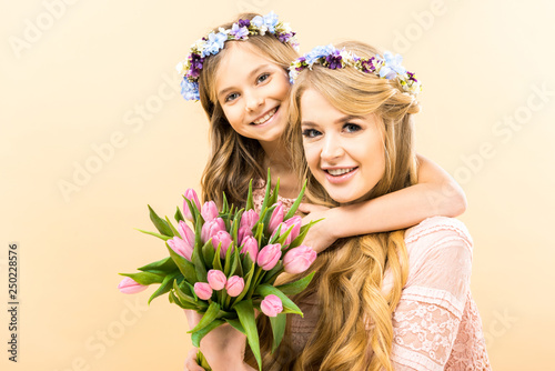 Leinwandbild Motiv beautiful woman and adorable daughter holding bouquet of pink tulips and looking at camera on yellow background