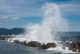 A large sea wave breaks about a breakwater. Close-up. Seascape