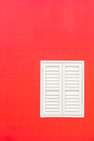 Simple duotone white closed window and bright red wall of building exterior flat facade with space for text