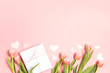 Romantic floral background with tulips flowers, gift and hearts on pink pastel background.