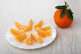 Tangerine with leaves, slices of tangerine in plate on table