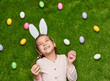 Cheerful girls with Easter eggs on lawn