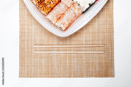 Two chopsticks, sushi and rolls in disposable packaging on wicker light background - 250282901