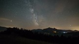 Milky way galaxy over mountains in starry night sky Time lapse
