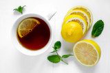 Photo of a cup of tea with lemon and mint. White cup of tea with lemon. Drink for convalescence. Vitamin C. - 250304710