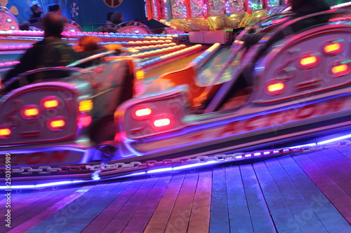 disco lights synthwave neon fairground ride night lights funfair amusement park moving, light trails, slow shutter-speed long exposure illuminations futuristic sci fi  - 250305989