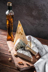 still life with cheese. Cheese maasdamer, brie, camembert, vinograd, med. On a wooden table with wine