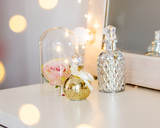 Perfume bottles and rose near mirror on a table
