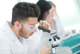 close up.man scientist looking through a microscope