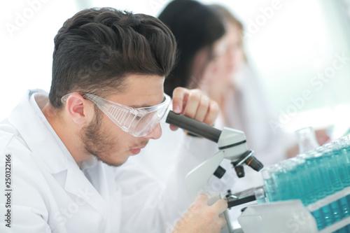 close up.man scientist looking through a microscope © yurolaitsalbert