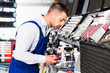 Professional car painter preparing paints for paintwork in modern auto repair shop
