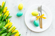 Festive traditional Easter dinner concept. Tableware, painted eggs, tulips flowers on white stone table top view