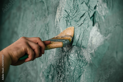 man holding the professional paintbrush with green background