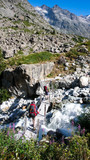 two hikers cross a creek over a small wooden bridge in the French Alps