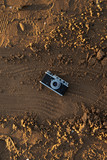 The camera on sand, sand texture with the ancient camera