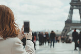 Fototapeta Wieża Eiffla - Girl takes pictures of a Eiffel Tower on a smartphone © Sergii Mostovyi