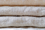 Neatly folded woven linen fabric in neutral shade