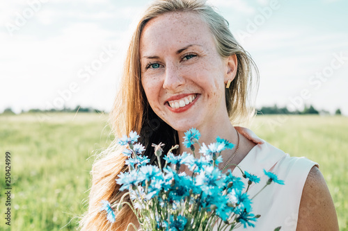 Leinwanddruck Bild Young woman with bouquet of cornflowers