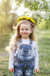 Leinwanddruck Bild - Spring sunny portrait of a cute 4 year old girl posing with a dandelion wreath, looking at the camera