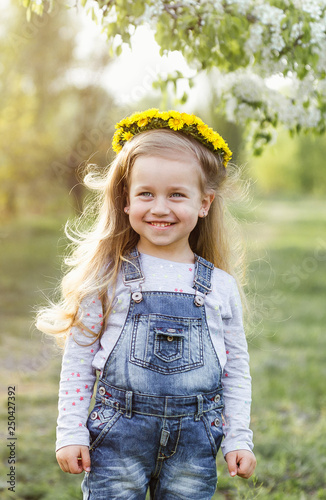 Leinwanddruck Bild Spring sunny portrait of a cute 4 year old girl posing with a dandelion wreath, looking at the camera