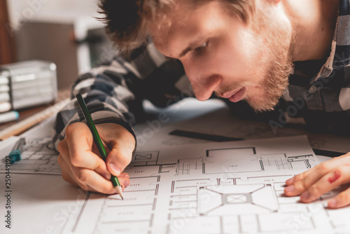 Foto Murales portrait of young architector at the work with pencil b