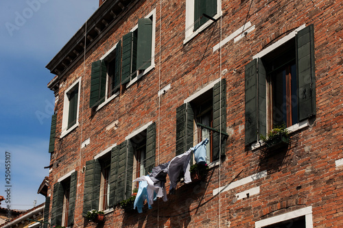 facade of an old house with dried laundry in the street, Italy - 250455107