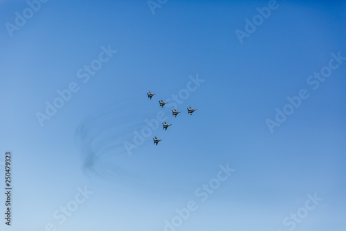 obraz PCV a triangular formation of a group of six russian military fighter jet planes flying high in blue sky