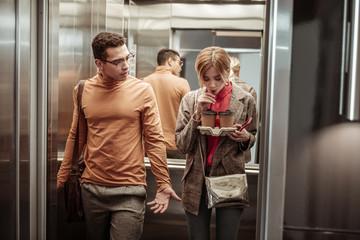 Slim blonde-haired girlfriend drinking coffee in the elevator
