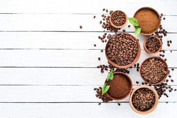 Ground coffee and coffee beans. On a white wooden background. Top view. Free space for your text.