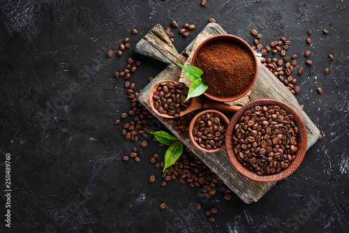 Leinwandbild Motiv Ground coffee and coffee beans. Assortment of coffee varieties on a black background. Top view. Free space for your text.