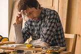 Carpenter planning DIY project in woodwork workshop