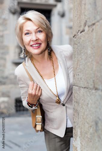 obraz lub plakat Elegant mature woman is posing near old wall
