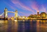 London cityscape at night with famous Tower Bridge illuminated and reflected in Thames river in England - UK