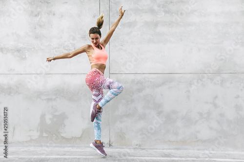 Dancer in fashion sportswear jumping over gray wall - 250550721
