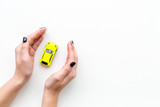 Car insurance concept. Safety of auto. Car toy in female hands on white background top view copy space