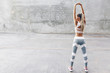 Fitness sport woman in fashion sportswear doing stretching exercise over gray wall